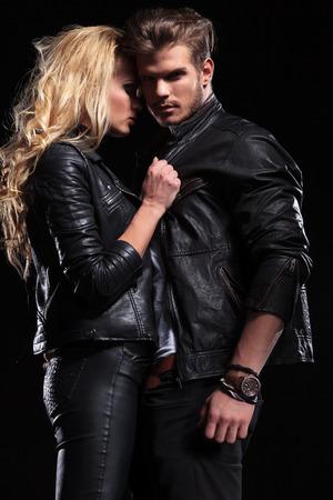 rocker girl: un hombre joven que mira a la cámara mientras sostiene a su novia que está tirando de su cuello.