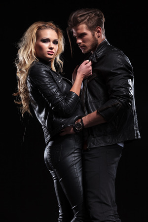 young blonde woman pulling her boyfriend by his jackets collars while looking into the camera he is holding her by the hips and looking at her .  photo