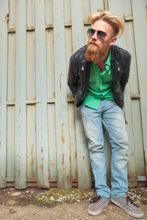 bending forward: young casual redhead bearded man bending forward and looking away from the camera