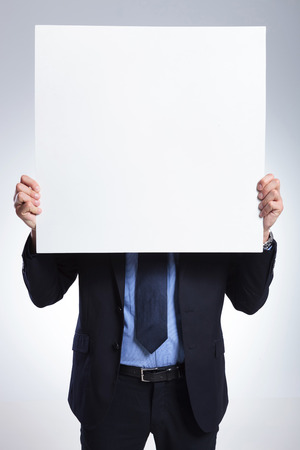 pannel: young business man holding a blank pannel in front of him.