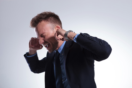 plugging: young business man plugging his ears with his fingers and closing his eyes while screaming. on a light gray studio background