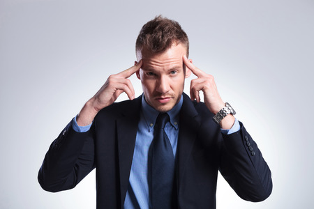 office force: young business man concentrating with his fingers at his temples while looking into the camera. on a light gray studio background