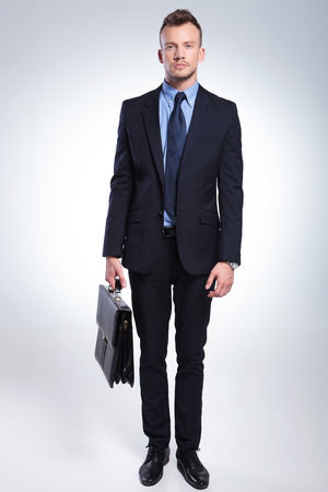brief case: portrait of a young business man with a briefcase in his hand, looking into the camera. on a gray background