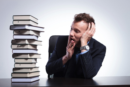 young business man sitting at his desk and looking with his hand at his mouth at a big stack of books. on a light studio background photo