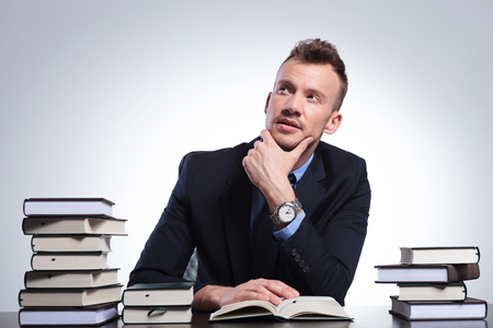 wondering: young business man at his office reading a book and thinking while looking up with his hand at his chin. on a light studio background Stock Photo