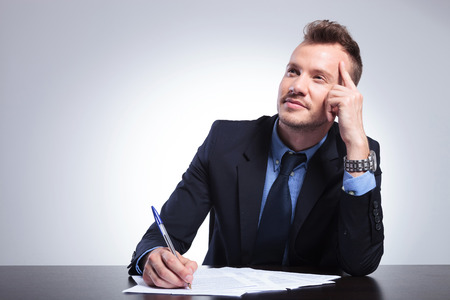 businessman pondering documents: young business man sitting at the desk and thinking of what to write while looking away. on a light gray studio backgroud