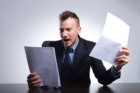 shocked: young business man in shock after reading his bills. on a light gray studio backgroud