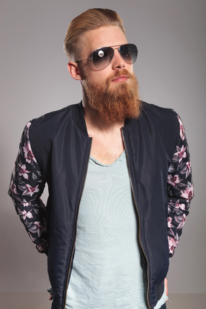bearded: casual young man with a long red beard holding both hands in his rear pockets and looking away from the camera. on gray studio background Stock Photo