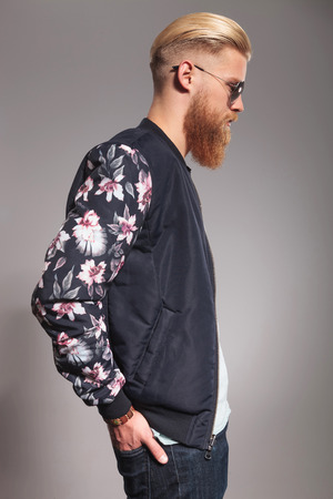 side view of a casual young man with a long red beard holding his hands in his back pockets and looking forward, away from the camera. on gray studio background photo