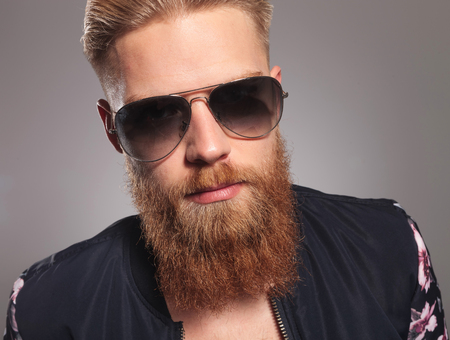 close up picture of a casual young man with a long red beard, looking into the camera. on gray studio background photo