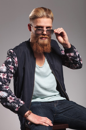 sitting down: casual young man with a long red beard sitting and looking into the camera while taking off his sunglasses. in a gray background studio
