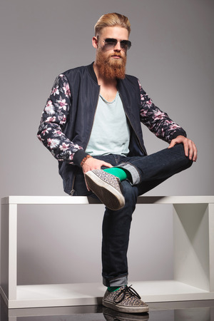 man legs: casual young man with a long red beard sitting on a small table and holding his legs crossed while looking into the camera. in a gray background studio