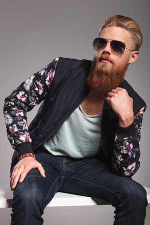 casual young man with a long red beard sitting in a pensive pose and looking away from the camera.
