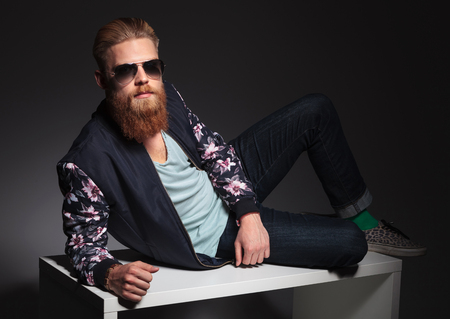 full grown: full length picture of a relaxed young bearded man laying on a studio table and looking into the camera. on a black studio background