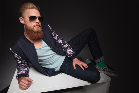 young bearded hipster laying down on a studio table and looking into the camera. on a black studio background photo