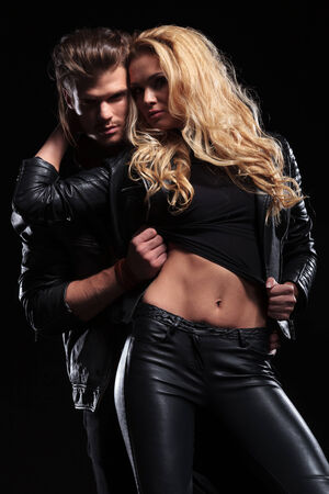 young man standing behind his woman and pulling up her shirt, revealing her beautiful abs while looking into the camera . on black background photo
