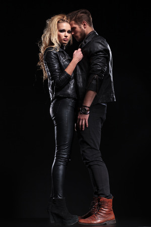 leather boots: full length picture of a beautiful couple posing on a black studio background