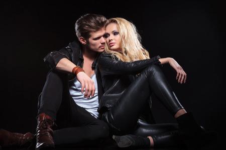 rocker girl: Mujer joven y guapo sentado en el suelo con su novio y mirándolo por encima del hombro. sobre fondo negro