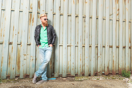 full grown: full length portrait of a young casual redhead bearded man standing outdoor with his hands in his pockets and looking away from the camera Stock Photo
