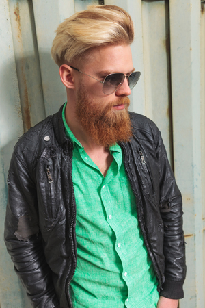 young casual redhead bearded man posing outdoor and looking down, away from the camera photo