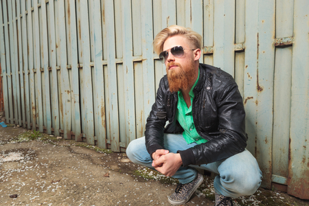 crouched: young casual redhead bearded man squatting next to an iron fence and holding his hands together while looking away from the camera