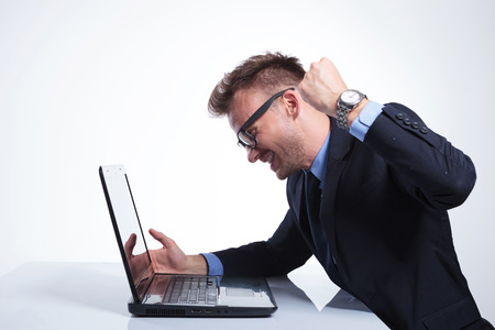 slow: side view of an angry young business man wanting to punch his laptop. on a gray studio backgroud Stock Photo