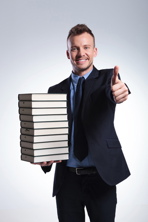young business man with many books in one hand shows the thumb up gesture while smiling for the camera. on a light studio background photo