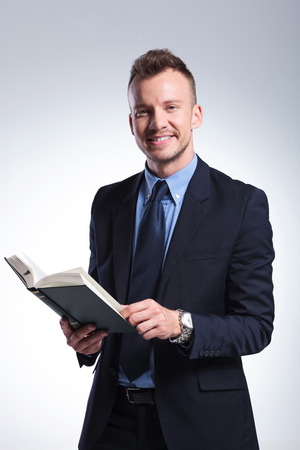 young business man smiling for the camera while holding a book in his hand. on a light studio background Stock Photo - 27838154