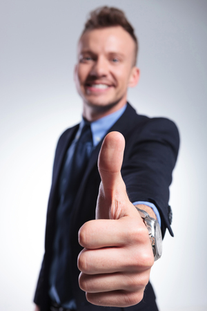 close up of a young business mans thumb up gesture. on a light gray studio background