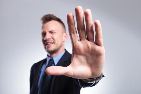 giovane uomo d'affari che li arresta con la mano. su uno studio di sfondo grigio chiaro