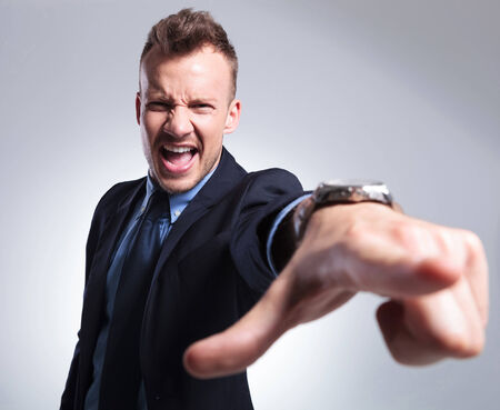 angry hand: angry young business man shouting and pointing at the camera. gray background Stock Photo