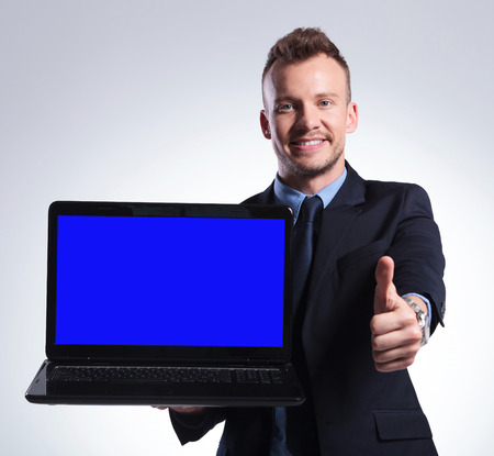 young business man holding his laptop in one hand and showing the thumb up gesture with the other while smiling for the camera. on a grey background photo
