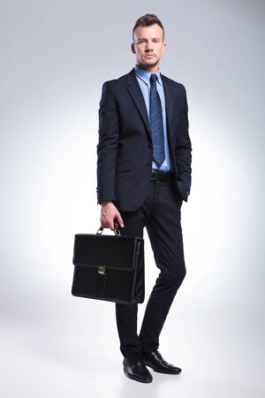 suit case: full length photo of a young business man holding his suitcase while holding a hand in his pocket and looking into the camera. on gray background