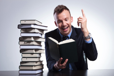 aha: young business man reading at an office with a stack of books and pointing up with a smile on his face, as he understands the idea. on a light studio background Stock Photo