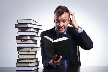 jonge zakenman het lezen van een moeilijk boek en krassen zijn hoofd tijdens de vergadering op zijn kantoor. op een lichte achtergrond studio