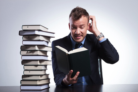 study desk: young business man reading a difficult book and scratching his head while sitting at his office. on a light studio background