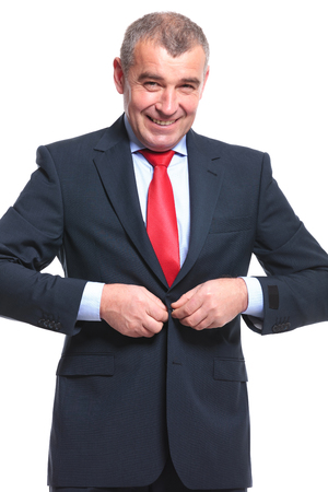 mature businessman: mid aged business man buttoning his suit jacket while smiling for the camera. isolated on a white