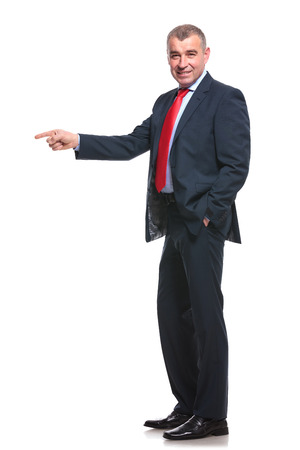 side view of a mid aged business man pointing forward while holding a hand in his pocket and smiling for the camera. isolated on a white