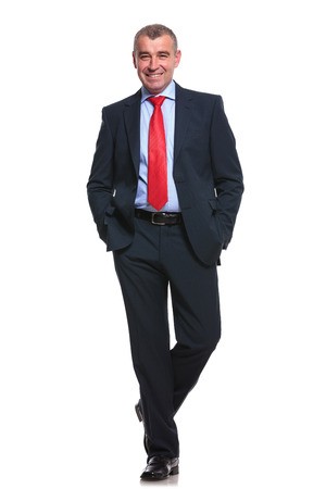 mature businessman: full length picture of a middle aged business man smiling for the camera with his hands in his pockets. isolated on a white