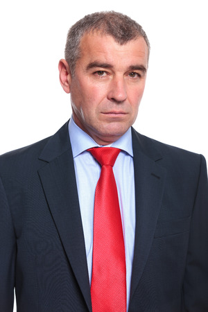 mature businessman: close up portrait of a middle aged business man looking into the camera with a serious expression. isolated on a white  Stock Photo