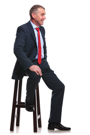stool: mid aged business man sitting on a chair and smiling away from the camera. isolated on a white  Stock Photo