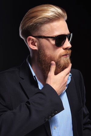 young business man looking away from the camera while holding his hand on his big red beard.  photo