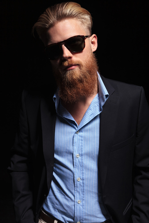 front view of a young bearded business man looking into the camera while holding both hands in his pockets.  photo