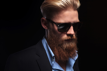 close up picture of a young bearded business man looking down, away from the camera.  photo