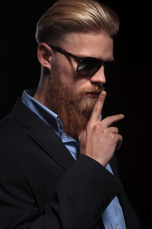 young bearded business man looking away from the camera while holding his finger at his mouth .  Stock Photo