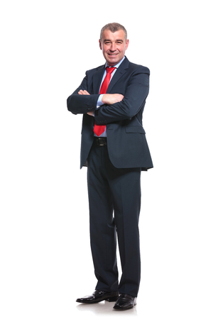 full length picture of a mid aged business man smiling with his arms crossed. isolated on a white  photo