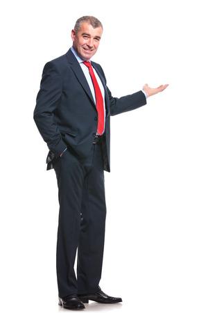 30 高齢者ビジネス男性が彼のポケットに手を握ってとカメラの笑顔しながら後ろに何かを示します。白で隔離