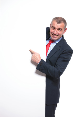 mid aged business man showing something on an empty board while smiling for the camera. isolated on a white  photo
