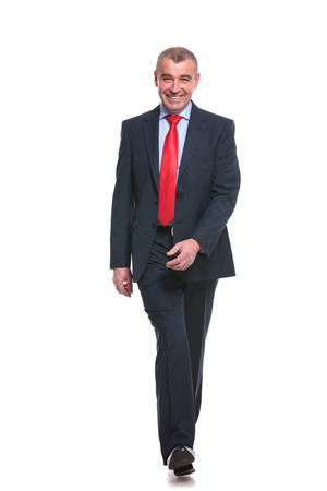 full length picture of a mid aged business man walking towards the camera and smiling. isolated on a white  photo