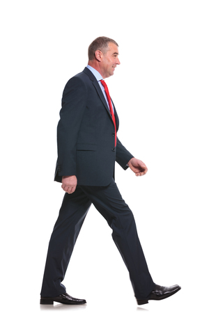 side view full length photo of a mid aged business man walking forward and looking away. isolated on a white  Stock Photo